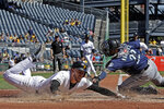 Pittsburgh Pirates' Joe Musgrove, left, slides around a tag-attempt by Seattle Mariners catcher Omar Narvaez to score on a single by Kevin Newman off Mariners starting pitcher Yusei Kikuchi during the second inning of a baseball game in Pittsburgh, Thursday, Sept. 19, 2019. (AP Photo/Gene J. Puskar)