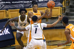 Tennessee's Yves Pons, top, passes the ball around Missouri's Xavier Pinson (1) and Kobe Brown, left, during the first half of an NCAA college basketball game Wednesday, Dec. 30, 2020, in Columbia, Mo. (AP Photo/L.G. Patterson)