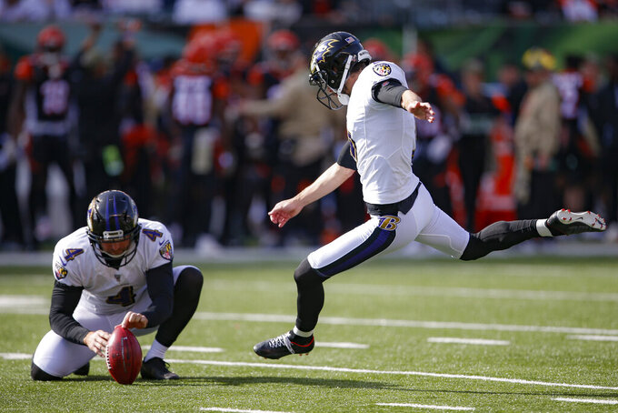 Baltimore Ravens kicker Justin Tucker, right, kicks an extra point during the first half of NFL football game against the Cincinnati Bengals, Sunday, Nov. 10, 2019, in Cincinnati. (AP Photo/Gary Landers)