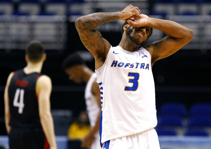Hofstra's Justin Wright-Foreman covers his face in the final seconds against Northeastern in an NCAA college basketball game at the Colonial Athletic Association men's basketball championship, Tuesday, March 12, 2019, in North Charleston, S.C. Northeastern defeated Hofstra 82-74. (AP Photo/Mic Smith)