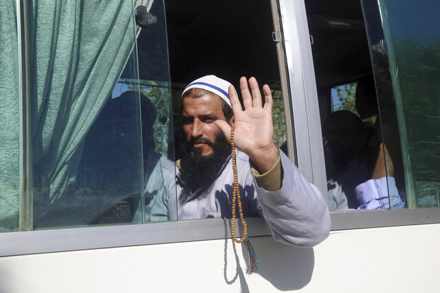 An Afghan Taliban prisoner waves from a bus after being freed from Bagram Prison in Parwan province, Afghanistan, Tuesday, May 26, 2020. The Afghan government freed hundreds of prisoners, its single largest prisoner release since the U.S. and the Taliban signed a peace deal earlier this year that spells out an exchange of detainees between the warring sides. (AP Photo/ Rahmat Gul)