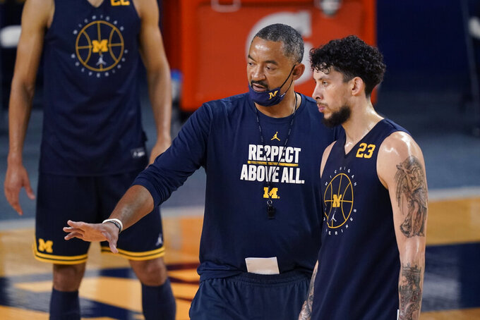 Michigan head basketball coach Juwan Howard, front left, talks with forward Brandon Johns Jr. (23) during an NCAA college basketball practice during media day, Friday, Oct. 15, 2021, in Ann Arbor, Mich. (AP Photo/Carlos Osorio)