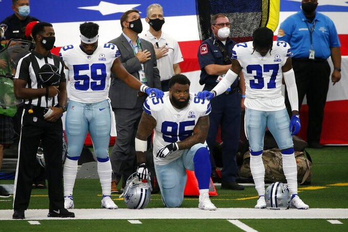 Dallas Cowboys' Justin March (59) and Donovan Wilson (37) place their hands on Dontari Poe (95) who knelt during the playing of the national anthem before an NFL football game against the Atlanta Falcons in Arlington, Texas, Sunday, Sept. 20, 2020. (AP Photo/Michael Ainsworth)