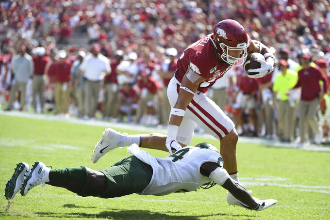 Arkansas tight end Chase Harrell slips past Colorado State defender Anthony Hawkins to score a touchdown during the first half of an NCAA college football game, Saturday, Sept. 14, 2019 in Fayetteville, Ark. (AP Photo/Michael Woods)