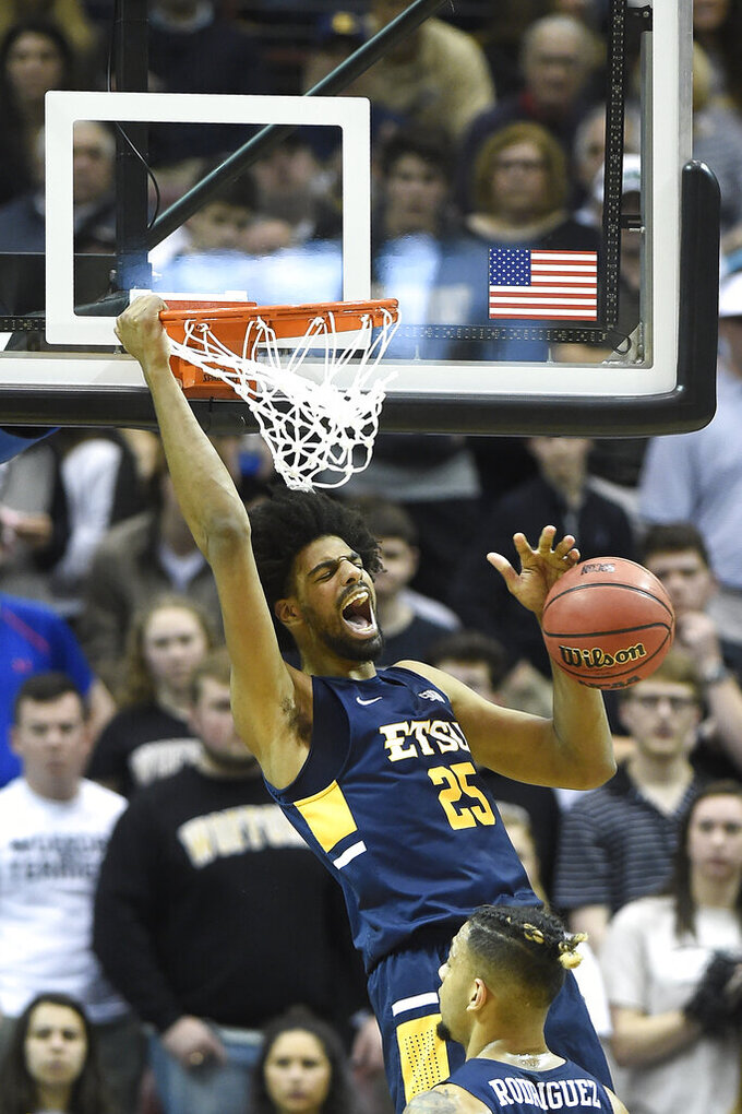 East Tennessee State center Lucas N'Guessan (25) dunks against Wofford in the first half of a semi-final NCAA college basketball game in the Southern Conference basketball tournament championship, Sunday, March 10, 2019, in Asheville, N.C. (AP Photo/Kathy Kmonicek)