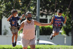 A woman and two children wear masks at a playground, Saturday, July 11, 2020, in Los Angeles. The number of deaths per day from the coronavirus in the U.S. had been falling for months, and even remained down as some states saw explosions in cases. But now a long-expected upturn has begun, driven by fatalities in states in the South and West. (AP Photo/Marcio Jose Sanchez)