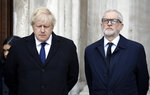 Britain's Prime Minister Boris Johnson, left, and Labour Party leader Jeremy Corbyn take part in a vigil at Guildhall Yard in London, Monday Dec. 2, 2019, to remember the London attack victims and honor members of the emergency services and bystanders who fought the attacker. London Bridge reopened to cars and pedestrians Monday, three days after a man previously convicted of terrorism offenses stabbed two people to death and injured three others before being shot dead by police. (AP Photo/Matt Dunham)