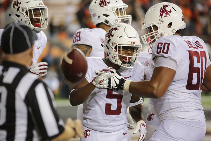 Washington State's Travell Harris (5) celebrates with teammate Andre Dillard (60) after making a touchdown during the fourth quarter of an NCAA college football against Oregon State in Corvallis, Ore., Saturday, Oct. 6, 2018. (AP Photo/Timothy J. Gonzalez)