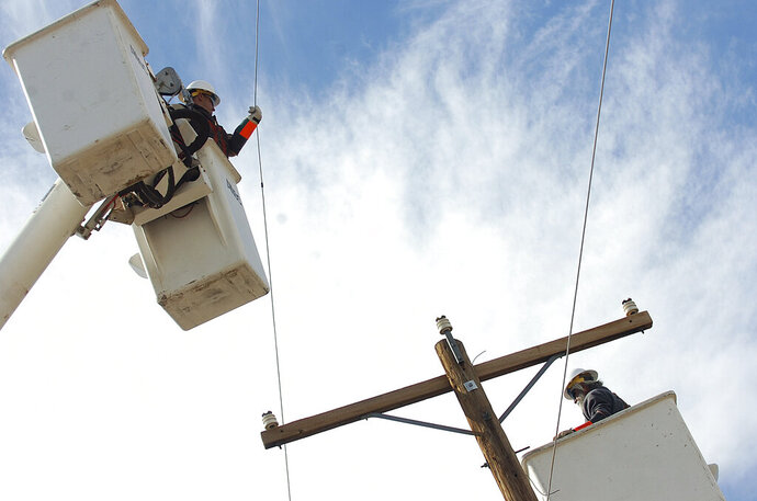 -Socorro Electric Cooperative linemen Juan Romero, left, and Henry Rosas work on a line just south of Socorro on Thursday March 20, 2008. (Adolphe Pierre-Louis/The Albuquerque Journal via AP)