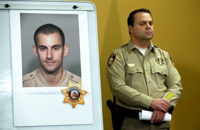 FILE - In this June 2, 2020, file photo, Las Vegas Police Assistant Sheriff Chris Jones stands by a photo of Metro Police officer Shay Mikalonis, 29, a four-year veteran of the department, during a media briefing at police headquarters in Las Vegas. A motel security guard told a judge on Thursday, Aug. 27, 2020, he was steps away and saw a man fire a handgun toward police and demonstrators on the Las Vegas Strip, critically wounding police officer Mikalonis. Juan Pablo Hernandez-Rodriguez testified he saw 20-year-old Edgar Samaniego pull a gun, cross his arms and shoot late June 1. Officer Shay Mikalonis was wounded in the head and left paralyzed. (Steve Marcus/Las Vegas Sun via AP)