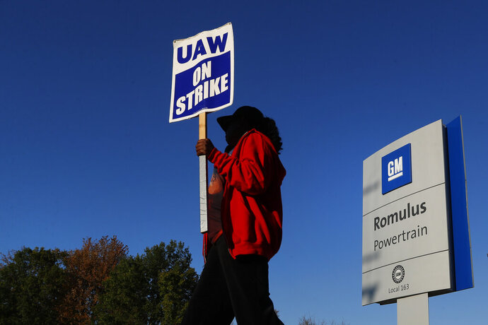 Yolanda Jacobs, a United Auto Workers member, walks the picket line at the General Motors Romulus Powertrain plant in Romulus, Mich., Wednesday, Oct. 9, 2019. Nearly four weeks into the United Auto Workers' strike against GM, employees are starting to feel the pinch of going without their regular paychecks. (AP Photo/Paul Sancya)