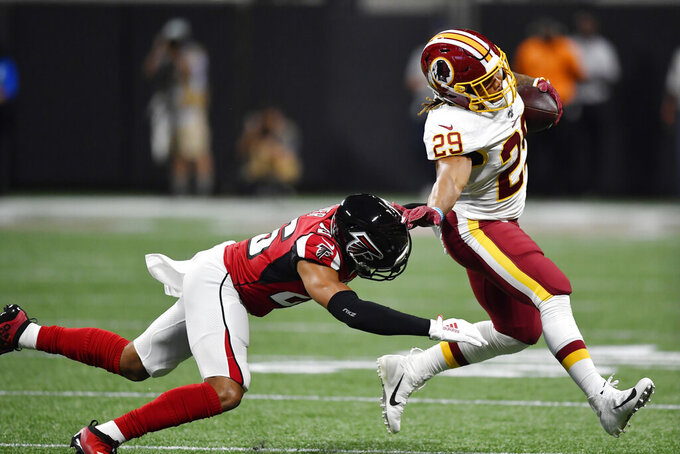 Atlanta Falcons free safety Isaiah Oliver (26) tackles Washington Redskins running back Derrius Guice (29) during the first half an NFL preseason football game, Thursday, Aug. 22, 2019, in Atlanta. (AP Photo/Mike Stewart)