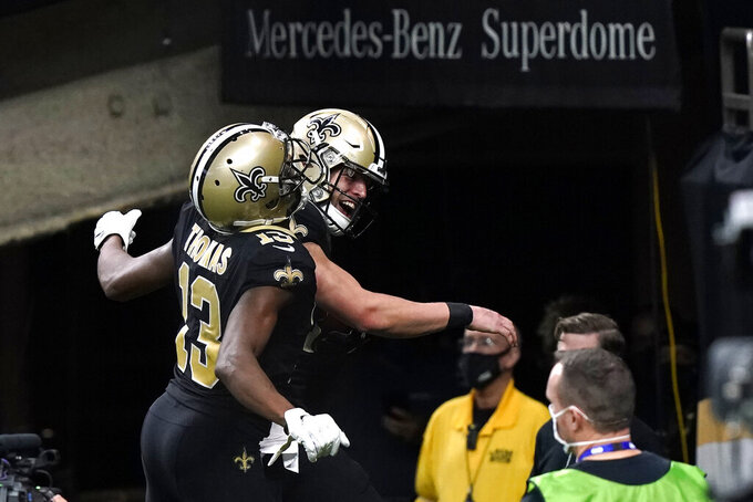 New Orleans Saints quarterback Taysom Hill celebrates his touchdown carry with wide receiver Michael Thomas (13) in the second half of an NFL football game against the Atlanta Falcons in New Orleans, Sunday, Nov. 22, 2020. (AP Photo/Butch Dill)