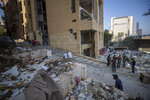 Workers remove debris from destroyed buildings near the site of last week's explosion that hit the seaport of Beirut, Lebanon, Wednesday, Aug. 12, 2020. (AP Photo/Hassan Ammar)