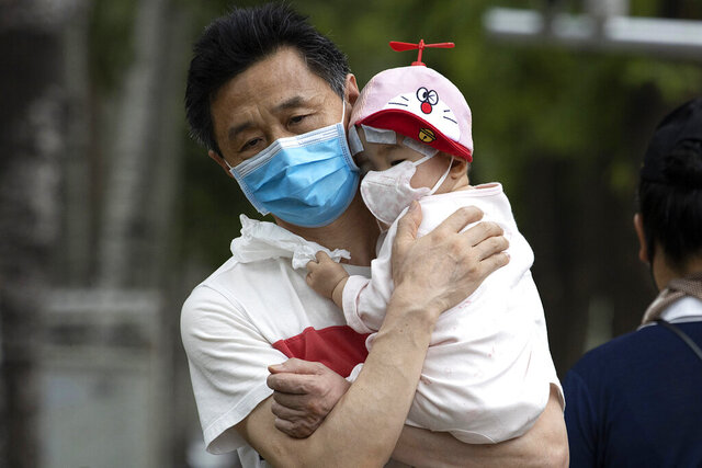 A man holds a child wearing masks to curb the spread of the coronavirus in Beijing on Wednesday, June 17, 2020. The Chinese capital on Wednesday canceled more than 60% of commercial flights and raised the alert level amid a new coronavirus outbreak, state-run media reported. (AP Photo/Ng Han Guan)