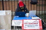 FILE- In this Monday, Jan. 11, 2021 file photo, elementary 1 teacher Melissa Vozar sits outside of Suder Elementary in Chicago to teach a virtual class. The Chicago Teachers Union said Sunday, Jan. 24 that its members voted to defy an order to return to the classroom before they are vaccinated against the coronavirus, setting up a showdown with district officials who have said such a move would amount to an illegal strike.  (Anthony Vazquez/Chicago Sun-Times via AP, File)