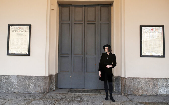 United States' soprano Lisette Oropesa poses in front of La Scala opera theater in Milan, Italy, Saturday, Dec. 5, 2020. Soprano Lisette Oropesa was to be the first American to single a title role in the gala season opener of La Scala since Maria Callas in the 1950s. Then Italy's virus cases surged, with an outbreak in both La Scala's chorus and orchestra, forcing Italy's premier opera house to cancel one of the top events on the European cultural calendar for the first time. Oropesa is one of 24 singers recording for a broadcast event marking the traditional Dec. 7 opening. (AP Photo/Antonio Calanni)