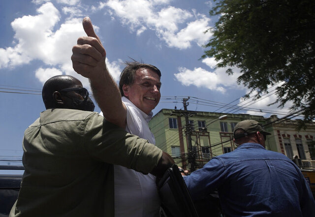Brazil's President Jair Bolsonaro greets supporters after voting during the run-off municipal elections in Rio de Janeiro, Brazil, Sunday, Nov. 29, 2020. Bolsonaro, who sometimes has embraced the label