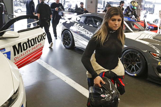 Hailie Deegan walks through her garage before the start of a practice session during testing for the upcoming Rolex 24 hour auto race at Daytona International Speedway, Friday, Jan. 3, 2020, in Daytona Beach, Fla. (AP Photo/John Raoux)