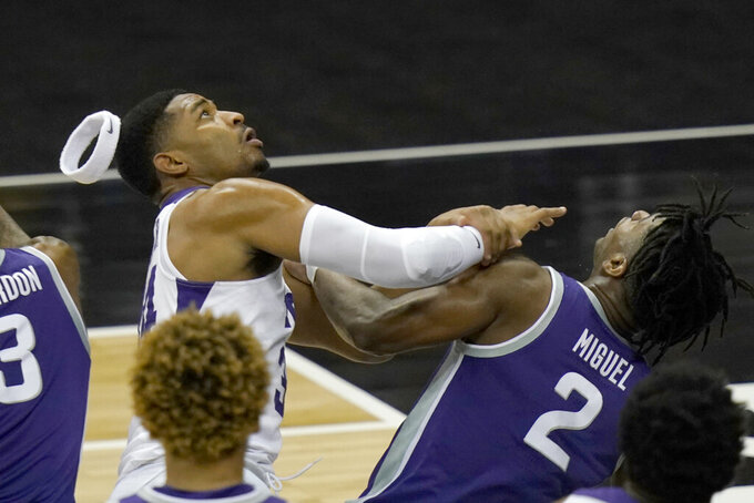 TCU forward Kevin Easley, left, loses his headband while he and Kansas State guard Selton Miguel (2) look for a rebound during the first half of an NCAA college basketball game in the first round of the Big 12 men's tournament in Kansas City, Mo., Wednesday, March 10, 2021. (AP Photo/Orlin Wagner)