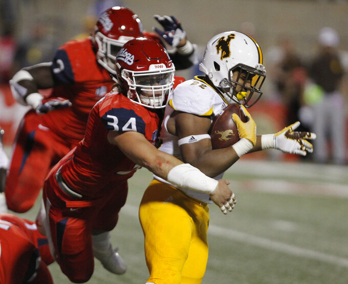 Wyoming running back Nico Evans is tackled by Fresno State linebacker George Helmuth during the first half of an NCAA college football game in Fresno, Calif., Saturday, Oct. 13, 2018. (AP Photo/Gary Kazanjian)