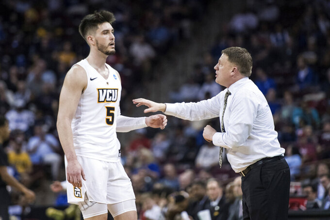 VCU head coach Mike Rhoades, right, talks with forward Sean Mobley (5) during the first half of a first-round game in the NCAA men's college basketball tournament Friday, March 22, 2019, in Columbia, S.C. (AP Photo/Sean Rayford)