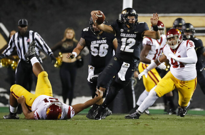 Colorado quarterback Steven Montez, center, gets away from Southern California defensive linemen Marlon Tuipulotu, left, and Brandon Pili during the first half of an NCAA college football game Friday, Oct. 25, 2019, in Boulder, Colo. (AP Photo/David Zalubowski)