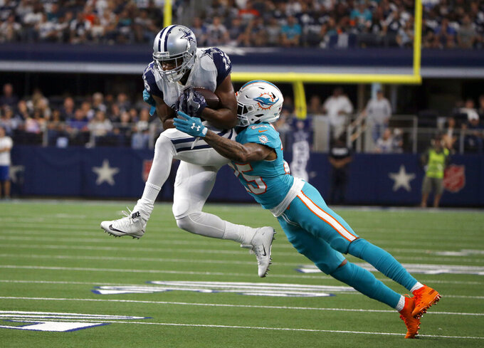 Dallas Cowboys wide receiver Amari Cooper, left, catches a pass for a first down as Miami Dolphins cornerback Xavien Howard (25) defends in the first half of an NFL football game in Arlington, Texas, Sunday, Sept. 22, 2019. (AP Photo/Michael Ainsworth)