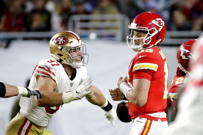 San Francisco 49ers' Nick Bosa, left, forces Kansas City Chiefs quarterback Patrick Mahomes to fumble, which Mahomes recovered, during the second half of the NFL Super Bowl 54 football game Sunday, Feb. 2, 2020, in Miami Gardens, Fla. (AP Photo/Patrick Semansky)