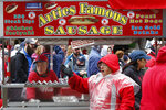 FILE - In this April 20, 2015 file photo, vendors hawk sausages outside Fenway Park before a baseball game between the Boston Red Sox and the Baltimore Orioles in Boston. Ballpark area businesses are struggling during the 2020 season while fans are not in attendance due to the COVID-19 pandemic. (AP Photo/Michael Dwyer, File)