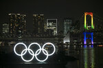 The illuminated Olympic rings float in the water near the Rainbow Bridge during a ceremony held to celebrate the 6-months-to-go milestone for the Tokyo 2020 Olympics Friday, Jan. 24, 2020, in the Odaiba district of Tokyo. (AP Photo/Jae C. Hong)