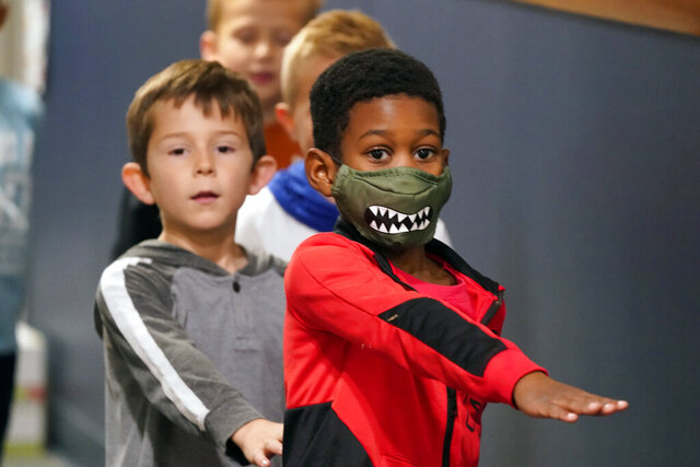 Students waking in the hallway at Tibbals Elementary School place their arms in front as a reminder to socially distance in Murphy, Texas, Thursday, Dec. 3, 2020. Texas Gov. Greg Abbot's statewide mask order does not mandate face covering for children under the age of 10, allowing some school districts to not require masks for children leaving the choice of mask use up to the parents. (AP Photo/LM Otero)