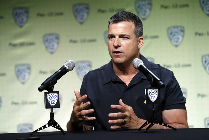 File-This July 24, 2019, file photo shows Oregon head coach Mario Cristobal answering questions during the Pac-12 Conference NCAA college football Media Day in Los Angeles. Cristobal figures the Ducks will have 19 days of traditional fall camp before they start preparing for Auburn. Oregon's opener, a rematch of sorts of the 2011 national championship game, is set for Aug. 31 at AT&T Stadium in Arlington, Texas.(AP Photo/Marcio Jose Sanchez, File)