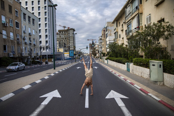 An Israeli man stands on his hands on an empty road during a lockdown following government measures to help stop the spread of the coronavirus, in Tel Aviv, Israel, Wednesday, April 8, 2020. Israeli Prime Minister Benjamin Netanyahu announced Monday a complete lockdown over the upcoming Passover holiday to control the country's virus outbreak, but offered citizens some hope by saying he expects to lift widespread restrictions after the week-long Jewish holiday of Passover. (AP Photo/Oded Balilty)