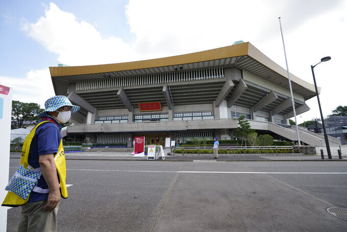 A volunteer works outside the Nippon Budokan stadium for judo ahead of the 2020 Summer Olympics, Friday, July 23, 2021, in Tokyo, Japan. (AP Photo/Vincent Thian)