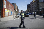 An NYPD traffic officer wearing personal protective equipment directs vehicles at a barricade after the city closed down a section of Bushwick Avenue due to COVID-19 concerns, Friday, March 27, 2020, in the Brooklyn borough of New York. The new coronavirus causes mild or moderate symptoms for most people, but for some, especially older adults and people with existing health problems, it can cause more severe illness or death. (AP Photo/John Minchillo)