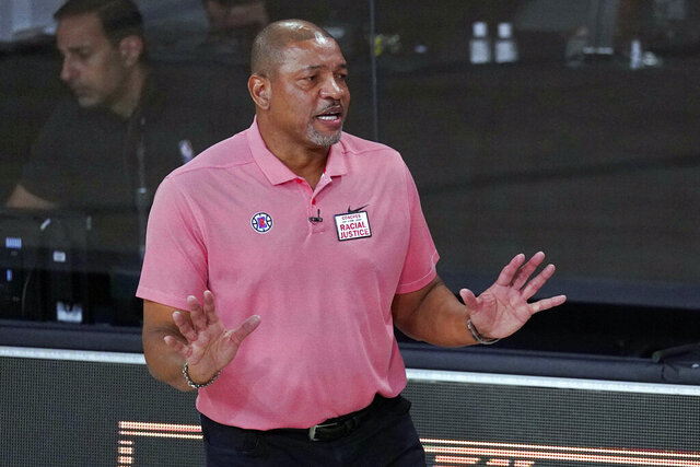 "FILE - In this Sept. 15, 2020, file photo, Los Angeles Clippers head coach Doc Rivers questions a call during the first half of an NBA conference semifinal playoff basketball game against the Denver Nuggets in Lake Buena Vista, Fla. Rivers is now head coach of the Philadelphia 76ers. The first preseason camps of the coronavirus era are formally open, with teams limited for now to individual sessions with one coach and one player at one basket, all of this starting to happen as the pandemic continues raging and more and more Americans are testing positive.  ""I'm very concerned if we can pull this off,"" Philadelphia coach Doc Rivers said.  (AP Photo/Mark J. Terrill, File)"