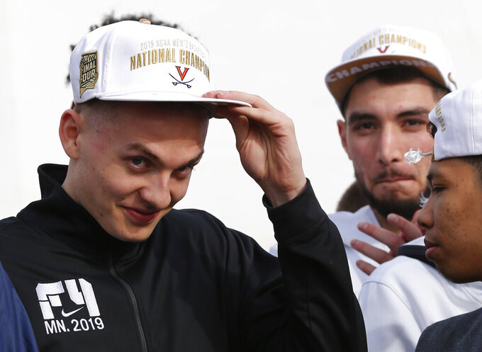 Tournament MVP Kyle Guy adjusts his hat as he is introduced during a welcoming ceremony as he and members of the Virginia basketball team are welcomed by fans as they return home after their win of the championship in the Final Four NCAA college basketball tournament against Texas Tech, in Charlottesville, Va., Tuesday, April 9, 2019. (AP Photo/Steve Helber)