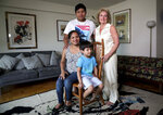In this Wednesday, Aug. 21, 2019 photo, Guatemalan immigrant Rosayra Pablo Cruz, far left, and her sons Yordy, 17, and Fernando, 6, pose with their host Vivien Tartter, a college professor who opened her home to the family for a year, in New York. Tartter is one more of a small but growing number of U.S. citizens who have picked up immigrants from detention centers, driven them to bus stations and doctor appointments, shared meals with them or hosted them at their homes, sometimes for one night, sometimes for a full year. (AP Photo/Bebeto Matthews)