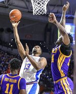 Florida center Kevarrius Hayes (13) shoots while defended by LSU forward Emmitt Williams, right, during the first half of an NCAA college basketball game in Gainesville, Fla., Wednesday, March 6, 2019. (AP Photo/Gary McCullough)