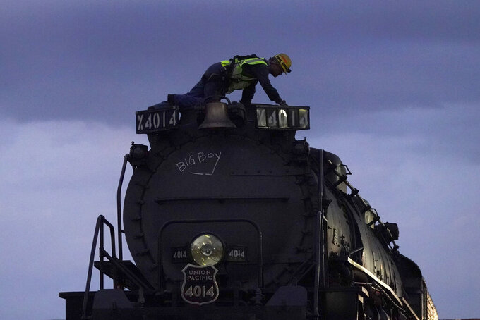 """FILE - In this Aug. 31, 2021, file photo, a worker tends to the world's largest operating steam locomotive, Union Pacific's Big Boy No. 4014, during an overnight stop in Kansas City, Mo. Cheyenne-based Big Boy No. 4014 returns home Tuesday, Sept. 7, 2021, from a month long tour of the nation. Led by Ed Dickens, the Union Pacific Heritage Steam program's showpiece is the massive locomotive that concluded its restoration in 2019 with a tour that marked the 150th anniversary of the completion of the Transcontinental Railroad, which became known as the """"overland route"""" which linked the nation. (AP Photo/Charlie Riedel, File)"""