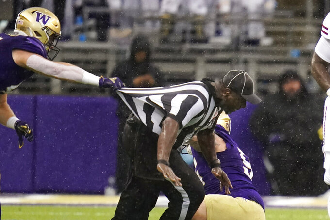 Washington's Cooper McDonald, left, tries to keep official Gregory Adams from tumbling after the umpire was caught between players in the first half of an NCAA college football game against Arkansas State, Saturday, Sept. 18, 2021, in Seattle. (AP Photo/Elaine Thompson)