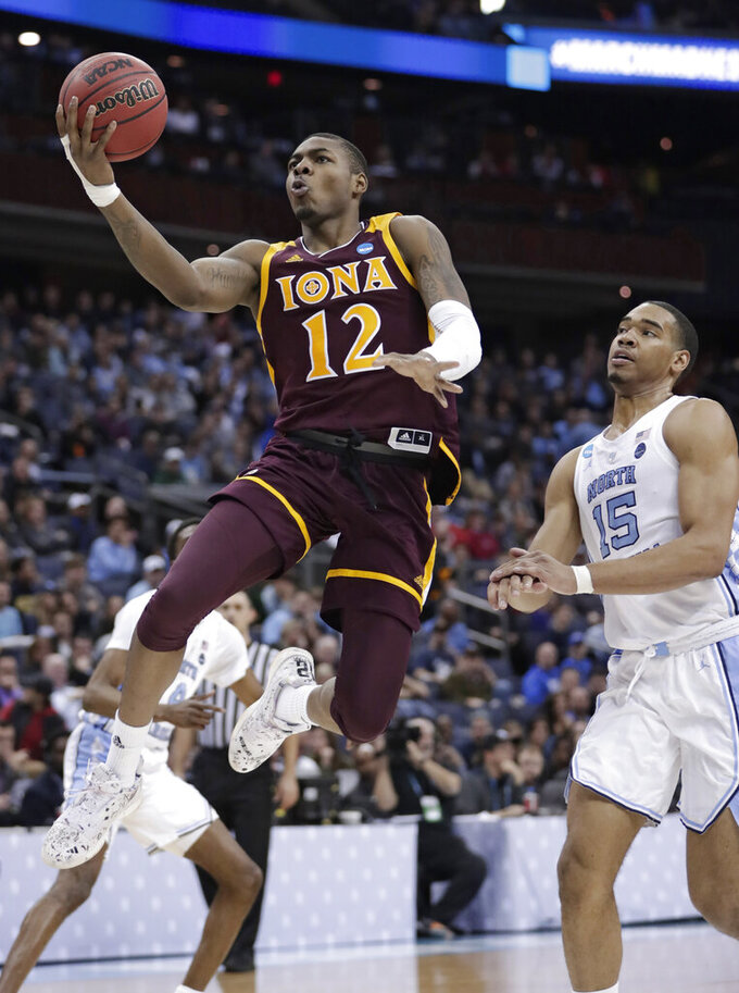 Iona's Tajuan Agee (12) drives to the basket against North Carolina's Garrison Brooks (15) during the second half of a first-round game in the NCAA men's college basketball tournament in Columbus, Ohio, Friday, March 22, 2019. North Carolina won 88-73. (AP Photo/Tony Dejak)