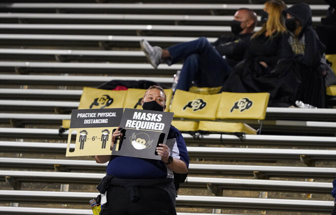 A guard holds up signs for rules to follow for fans to deal with the coronavirus in the first half of an NCAA college football game as Colorado hosts UCLA, Saturday, Nov. 7, 2020, in Boulder, Colo. (AP Photo/David Zalubowski)