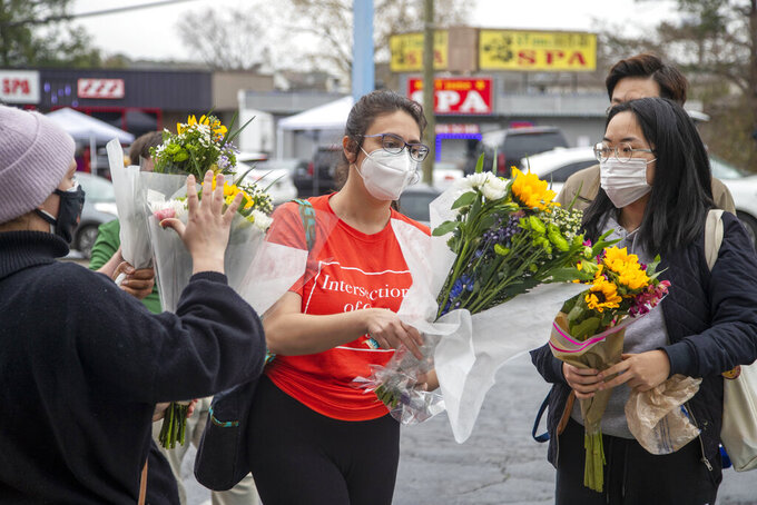 FILE - In this March 17, 2021, file photo, Roula AbiSamra, center, and Chelsey, right, prepare to lay flowers bouquets at a makeshift memorial outside of the Gold Spa in Atlanta. While the U.S. has seen mass killings in recent years where police said gunmen had racist or misogynist motivations, advocates and scholars say the shootings this week at three Atlanta-area massage parlors targeted a group of people marginalized in more ways than one, in a crime that stitches together stigmas about race, gender, migrant work and sex work. (Alyssa Pointer/Atlanta Journal-Constitution via AP, File)
