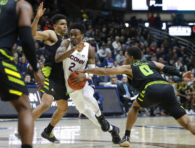 Connecticut's Tarin Smith, center, tries to drive past South Florida's Xavier Castaneda, center left, and David Collins, right, during the second half of an NCAA college basketball game, Sunday, March 3, 2019, in Storrs, Conn.(AP Photo/Steven Senne)