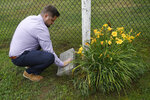Brett Eagleson, son of Sept. 11 victim Bruce Eagleson, wipes grass off a memorial stone for his father at the baseball field where his father use to coach, Friday, July 2, 2021, in Middletown, Conn. Eagleson and others who lost family on Sept. 11 are seeking the release of FBI documents that allege Saudi Arabia's role in the terrorist attacks. As the 20th anniversary of the Sept. 11 attacks nears, victims' relatives are using the courts to answer what they see as lingering questions about the Saudi government's role in the attacks. A lawsuit that accuses Saudi Arabia of being complicit took a major step forward this year with the questioning under oath of former Saudi officials, but those depositions remain under seal and the U.S. has withheld a trove of other documents as too sensitive for disclosure.  (AP Photo/Jessica Hill)