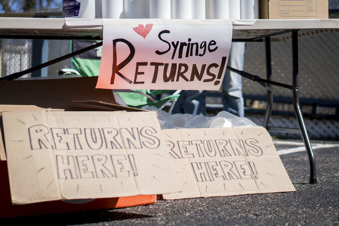 In this photo provided by Chad Cordell, signs for syringe returns are shown Saturday, March 6, 2021, at a nonprofit group's health fair in Charleston, W.Va. For years, West Virginia has had the nation's highest rate of drug overdose deaths. Now the state is wrestling with another, not entirely unrelated health emergency: a spike in HIV cases related to intravenous drug use. (Chad Cordell via AP)