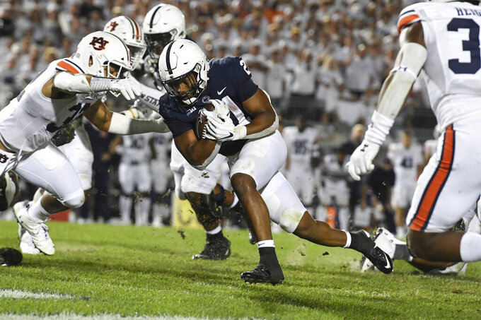 Penn State running back Noah Cain (21) lowers his shoulder to score a touchdown past Auburn linebacker Wesley Steiner (32) during the second half of an NCAA college football game in State College, Pa., on Saturday, Sept. 18, 2021. Penn State defeated Auburn 28-20. (AP Photo/Barry Reeger)