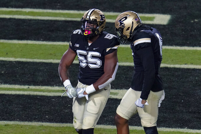 Purdue linebacker Derrick Barnes (55) celebrates a defensive stop with safety Jalen Graham (6) against Northwestern during the first half of an NCAA college football game in West Lafayette, Ind., Saturday, Nov. 14, 2020. (AP Photo/Michael Conroy)